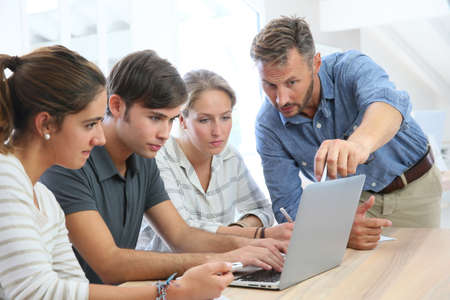 Teacher with group of students working on laptop computer