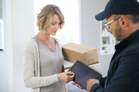 delivery person: Woman receiving package from delivery man