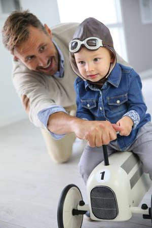 dad son: Man helping little boy on a riding toy