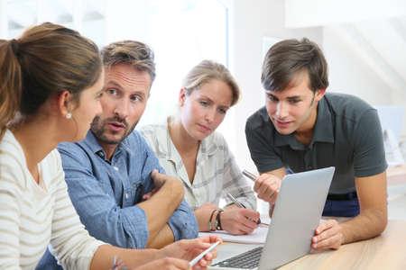 profesor alumno: Profesor con el grupo de estudiantes trabajando en equipo portátil