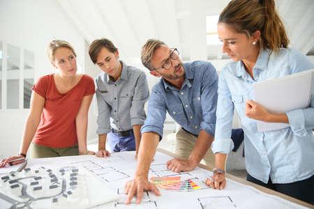 profesores: Los estudiantes con maestros que trabajan en proyecto alrededor de la mesa