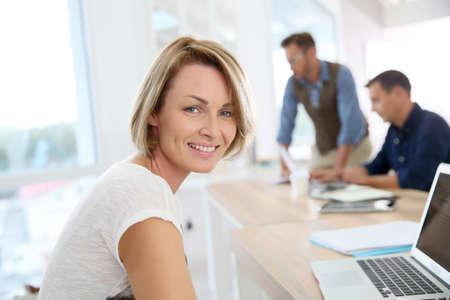 personas trabajando en oficina: Retrato de la mujer sonriente que trabaja en la oficina