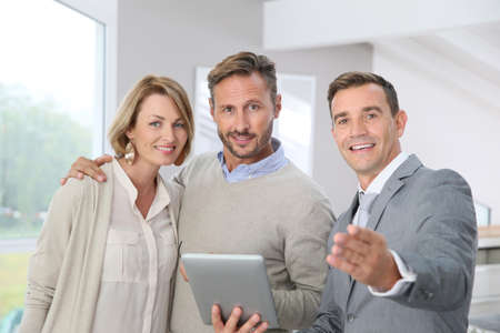 standing businessman: presenting new apartment to clients Stock Photo