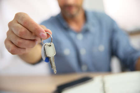 Real estate agent giving keys to property owner