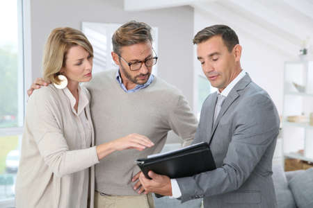 Real-estate agent showing house details on paper Stock Photo