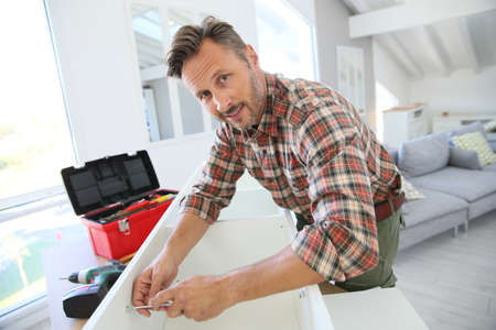 middleaged: Middle-aged man at home assembling furniture parts