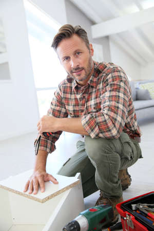 home furniture: Middle-aged man at home assembling furniture parts