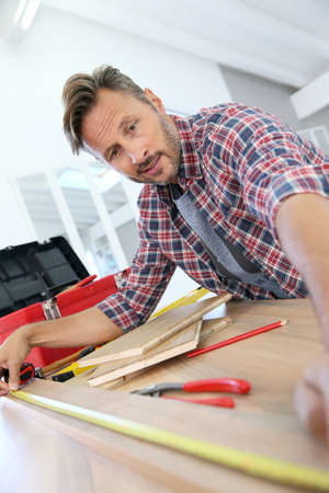 doityourself: Man working on wood planks for home-improvement