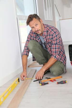 wood flooring: Cheerful man at home installing new wooden floor