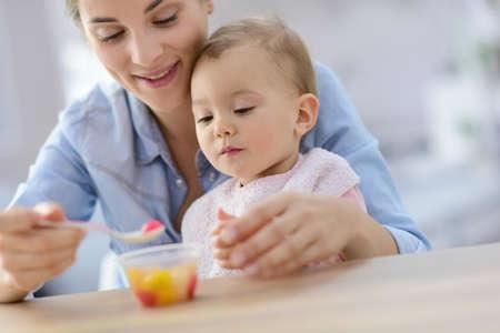 comiendo frutas: Joven madre ayudando a niña con comer por sí misma