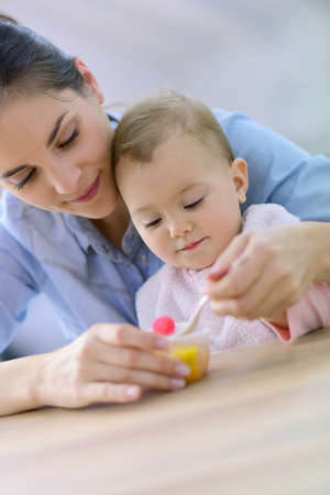 mother helping baby: Young mother helping baby girl with eating by herself