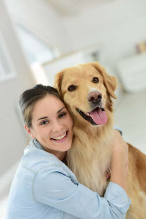 petting: Young woman petting her dog