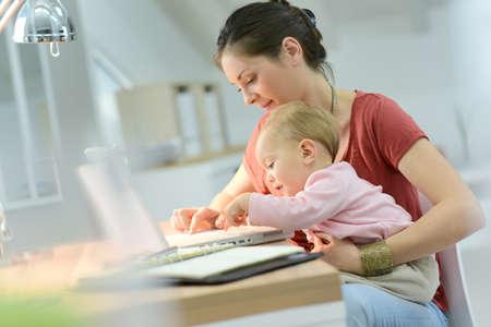 trabajando en casa: Mujer que trabaja desde su casa con el beb� en el regazo