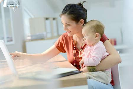 女性の膝の上の赤ちゃんを自宅から作業