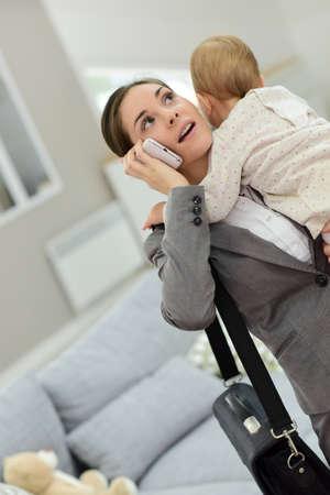 madre trabajando: Empresaria ocupada hablando por teléfono y la celebración de bebé en brazos Foto de archivo