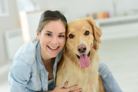 cuddles: Young woman petting her dog
