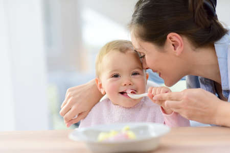 spoons: Baby girl eating lunch with help of her mommy