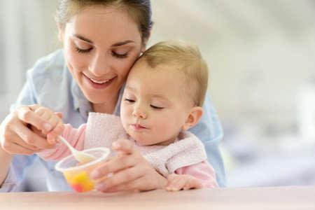 아기: 혼자 먹는 아기 소녀를 돕는 젊은 어머니