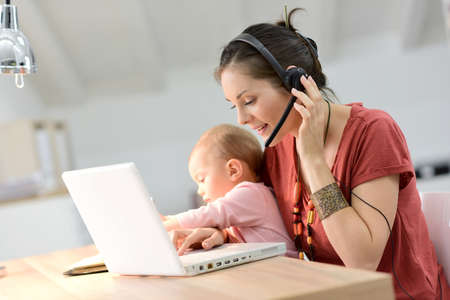 Busy businesswoman working with baby on lap