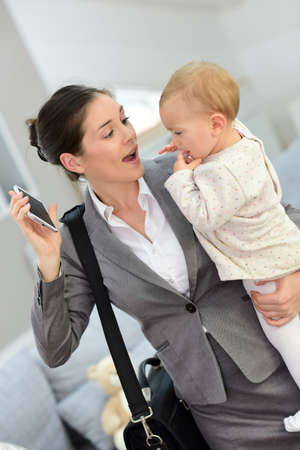 Busy businesswoman hurrying in the morning with baby in arms