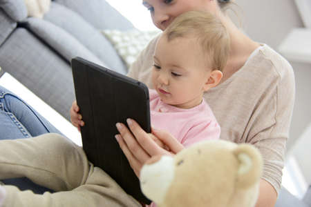 15 months old: Baby girl playing with digital tablet Stock Photo