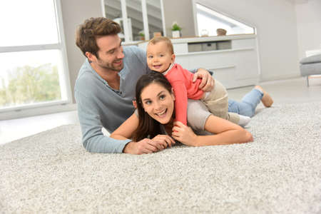Parents and baby girl laying on carpet, Stockfoto