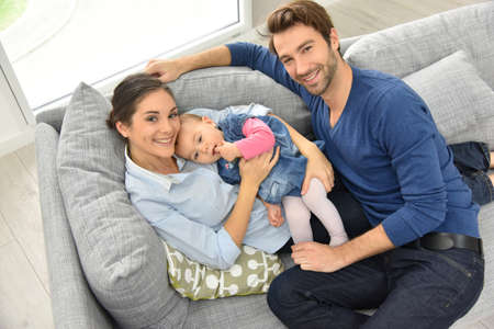 family sofa: Upper view of young family relaxing in sofa