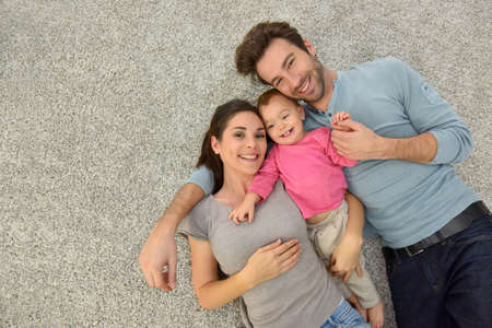 Upper view of family of three laying on carpet