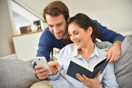entertaining: Couple at home entertaining and reading message on smartphone
