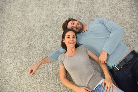 Upper view of couple laying on carpet