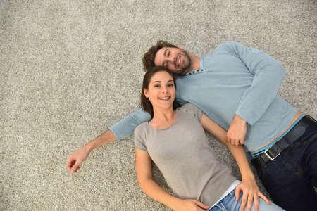 Vue de dessus d'un couple allongé sur le tapis Banque d'images