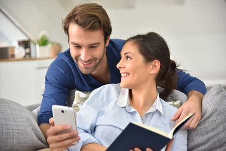 my home: Couple at home entertaining and reading message on smartphone