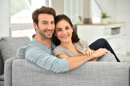 investment: Young couple relaxing in sofa Stock Photo