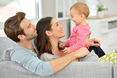 Couple with baby girl enjoying family time at home Reklamní fotografie