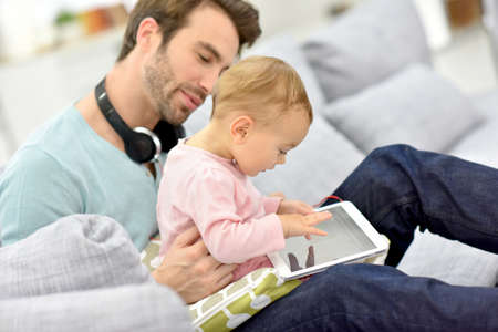 listening: Daddy and baby girl in sofa using tablet and headphones Stock Photo