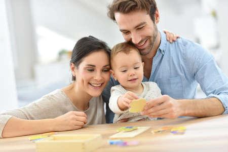 Les parents avec bébé fille jouant avec jeu en bois Banque d'images
