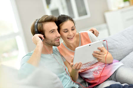 listening: Couple sitting in sofa and websurfing on digital tablet