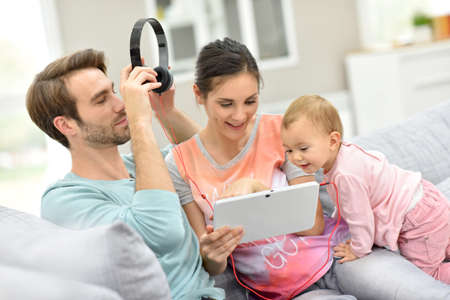 family playing: Couple with baby  in sofa watching movie on tablet