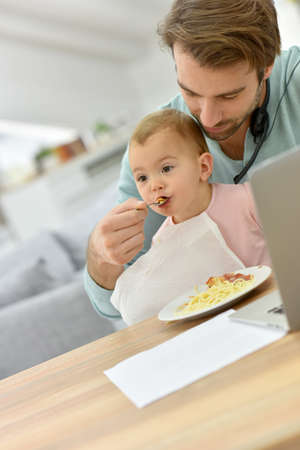 homeoffice: Man working from home and taking care of baby