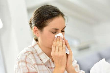 Jonge vrouw met een koud blazen haar neus Stockfoto