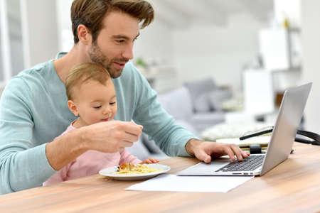 trabjando en casa: Hombre que trabaja desde su casa y el cuidado de bebé Foto de archivo