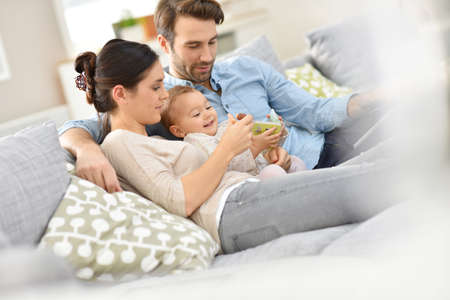family sofa: Family with baby in sofa watching tv Stock Photo