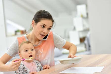 Mère occupée sur le téléphone bébé d'alimentation un même temps