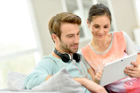 tablet: Couple sitting in sofa and websurfing on digital tablet