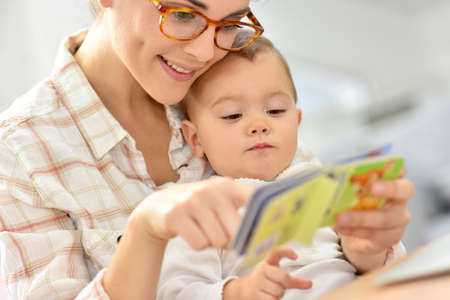 Sweet moment with mother reading book to baby Banco de Imagens