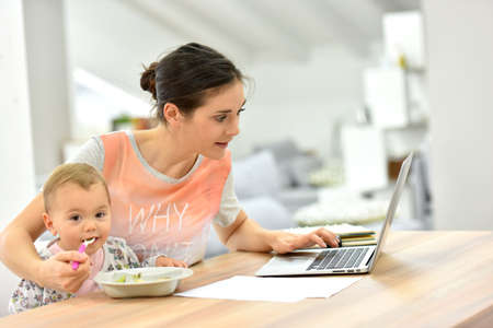 madre ocupada tratando de trabajar y alimentar niño al mismo tiempo,