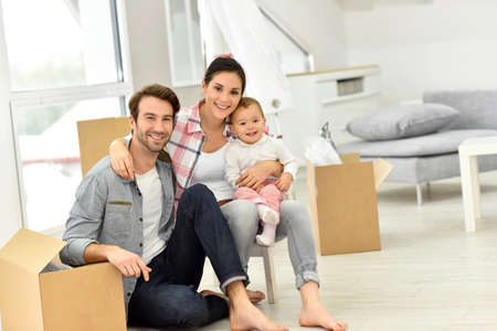 family indoors: Young family moving into new home