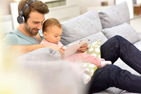 single parent: Daddy and baby girl in sofa using tablet and headphones Stock Photo