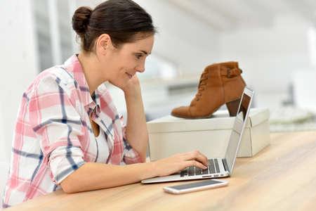 rendement: Jonge vrouw bestellen schoenen op internet Stockfoto