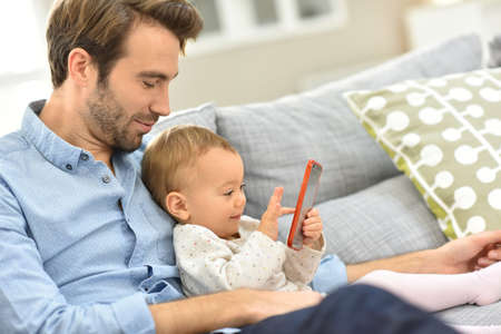 baby playing: Daddy and baby girl playing with smartphone Stock Photo